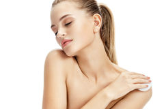 Sensual young woman cares for skin using cotton pad. stock photography