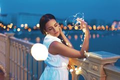 Sensual young woman with glowing fairy lights in bokeh on bridge royalty free stock photo