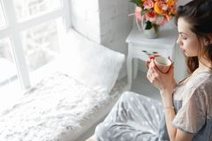 Sensual young woman with cup of tea. At home. Every morning ritual for good start of the day. Thoughtfulness and calmness, relaxation and perception concept Stock Image