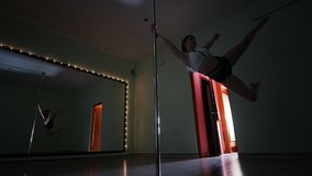 Sensual young woman dancing on the pole in a studio royalty free stock images
