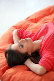 Sensual young woman dreaming on a blanket. Sensual young woman dreaming on an orange blanket Royalty Free Stock Image