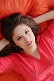 Sensual young woman dreaming on a blanket. Sensual young woman dreaming on an orange blanket Royalty Free Stock Images