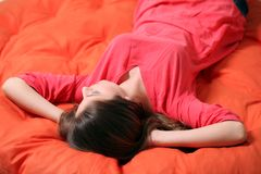 Sensual young woman dreaming on a blanket. Sensual young woman dreaming on an orange blanket Stock Image