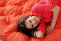 Sensual young woman dreaming on a blanket. Sensual young woman dreaming on an orange blanket Stock Photos