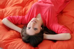 Sensual young woman dreaming on a blanket. Sensual young woman dreaming on an orange blanket Royalty Free Stock Photo