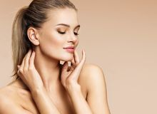 Sensual young woman enjoying her fresh clean skin. Portrait of beautiful woman of european appearance on beige background. Skin care and beauty concept royalty free stock photos