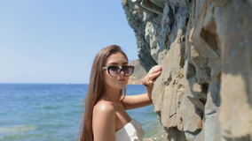 Sensual young woman with long straight hair in sunglasses and white bikini posing while standing in the sea near the stock video