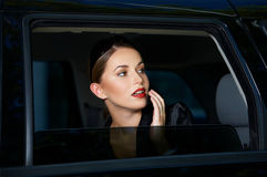 Sensual young woman looking out of a car window Royalty Free Stock Photos