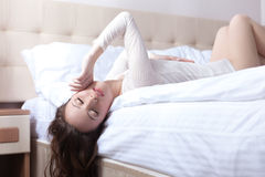 Sensual young woman lying on bed upside down Stock Image