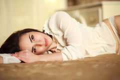 Sensual young woman lying in bedroom at home Royalty Free Stock Photography