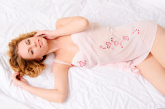 Sensual young woman in negligee on bed Stock Image