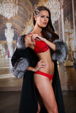 Sensual young woman with perfect slim body  in red lingerie and luxury fur coat posing sexy Stock Photo