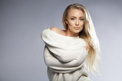 Sensual young woman posing in oversized sweater. Portrait of sensual young woman wearing oversized sweater looking at camera. Beautiful caucasian female fashion Stock Photo