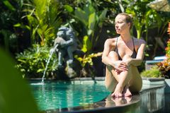 Sensual young woman relaxing in outdoor spa infinity swimming pool surrounded with lush tropical greenery of Ubud, Bali. Wellness, natural beauty and body care stock photography