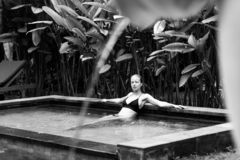 Sensual young woman relaxing in outdoor spa infinity swimming pool surrounded with lush tropical greenery of Ubud, Bali. Wellness, natural beauty and body care royalty free stock photo