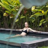 Sensual young woman relaxing in outdoor spa infinity swimming pool surrounded with lush tropical greenery of Ubud, Bali. Wellness, natural beauty and body care royalty free stock photography