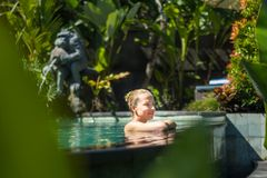 Sensual young woman relaxing in outdoor spa infinity swimming pool surrounded with lush tropical greenery of Ubud, Bali. Wellness, natural beauty and body care stock photos