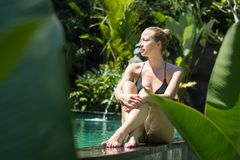 Sensual young woman relaxing in outdoor spa infinity swimming pool surrounded with lush tropical greenery of Ubud, Bali. Wellness, natural beauty and body care stock photo