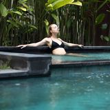 Sensual young woman relaxing in outdoor spa infinity swimming pool surrounded with lush tropical greenery of Ubud, Bali. Wellness, natural beauty and body care royalty free stock images