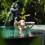 Sensual young woman relaxing in outdoor spa infinity swimming pool surrounded with lush tropical greenery of Ubud, Bali. Wellness, natural beauty and body care stock images