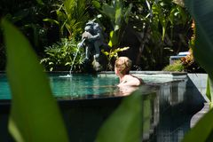 Sensual young woman relaxing in outdoor spa infinity swimming pool surrounded with lush tropical greenery of Ubud, Bali. Wellness, natural beauty and body care stock image