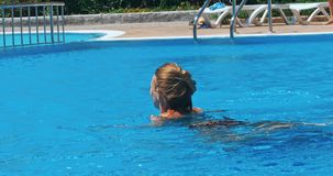 Sensual young woman relaxing in swimming pool. stock video footage