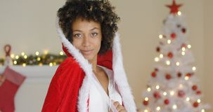 Sensual young woman in a Santa Claus outfit. Cuddling down inside the fur trimmed hood with a quiet friendly smile Stock Photography