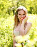 Sensual young woman, smiles sweetly in the flowered garden Stock Photography