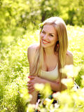 Sensual young woman, smiles sweetly in the flowered garden. Day dreaming stock photo