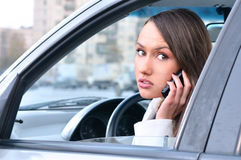 Sensual young woman is talking phone in car Stock Images