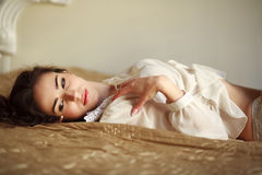 Sensual young woman thoughtfully lying on the bed at home Royalty Free Stock Photos