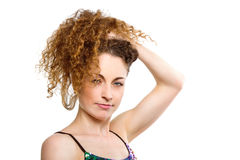 Sensual young woman touching her curly hair Royalty Free Stock Images