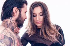 Sensual young woman touching a tattooed man. Sensual young women touching a tattooed men on white background Stock Photography