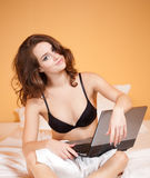 Sensual young woman using laptop. Royalty Free Stock Photos