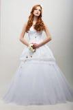 Sensualitet. Romantisk fästmö i den vita långa klänningen med buketten av blommor royaltyfria foton