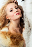 Sensuality attractive girl with foxy fur jacket. Sensuality young attractive girl with foxy fur jacket. Hand at face Stock Photography