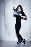Sensuality beautiful woman with long hairholding clapperboard. Sensuality beautiful woman with long hair, dressed in black posing in studio holding clapperboard Royalty Free Stock Photos
