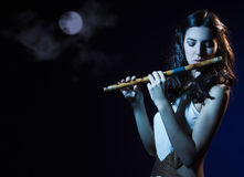 Sensuality brunette plays a wooden flute. Sensuality beauty brunette plays a wooden flute Royalty Free Stock Image