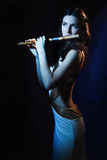 Sensuality brunette plays a wooden flute Royalty Free Stock Photography
