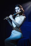 Sensuality brunette plays a wooden flute Stock Photos