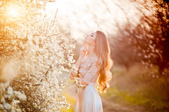 sensuality Den lyckliga härliga unga kvinnan som kopplar av i blomning, parkerar arkivfoto
