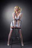 Sensuality gold blond woman stand with bar chair Royalty Free Stock Image