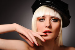 Sensuality model with blonde hair. Close up portrait of sensuality model with blonde hair and black peaked cap, isolated on grey. may be use for fashion cards Royalty Free Stock Photos