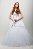 Sensuality. Romantic Fiancee in White Long Dress with Bouquet of Flowers Royalty Free Stock Photos