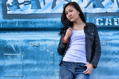 Sensuality woman in white T-shirt, black leather jacket, blue jeans and black long hair in the background blue urban iron Stock Photography