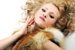 Sensuality young attractive girl with fur coat. Hand at face Royalty Free Stock Photo