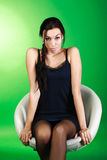 Sensuality young girl sitting on white chair in studio Royalty Free Stock Photography