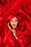 Sensueel gezicht in rode satijnstof Stock Afbeeldingen