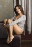 Sensueel meisje, die op bank gaan zitten, royalty-vrije stock foto