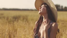 Sensueel portretclose-up van een mooi jong meisje in een strohoed op een wheaten gebied stock footage